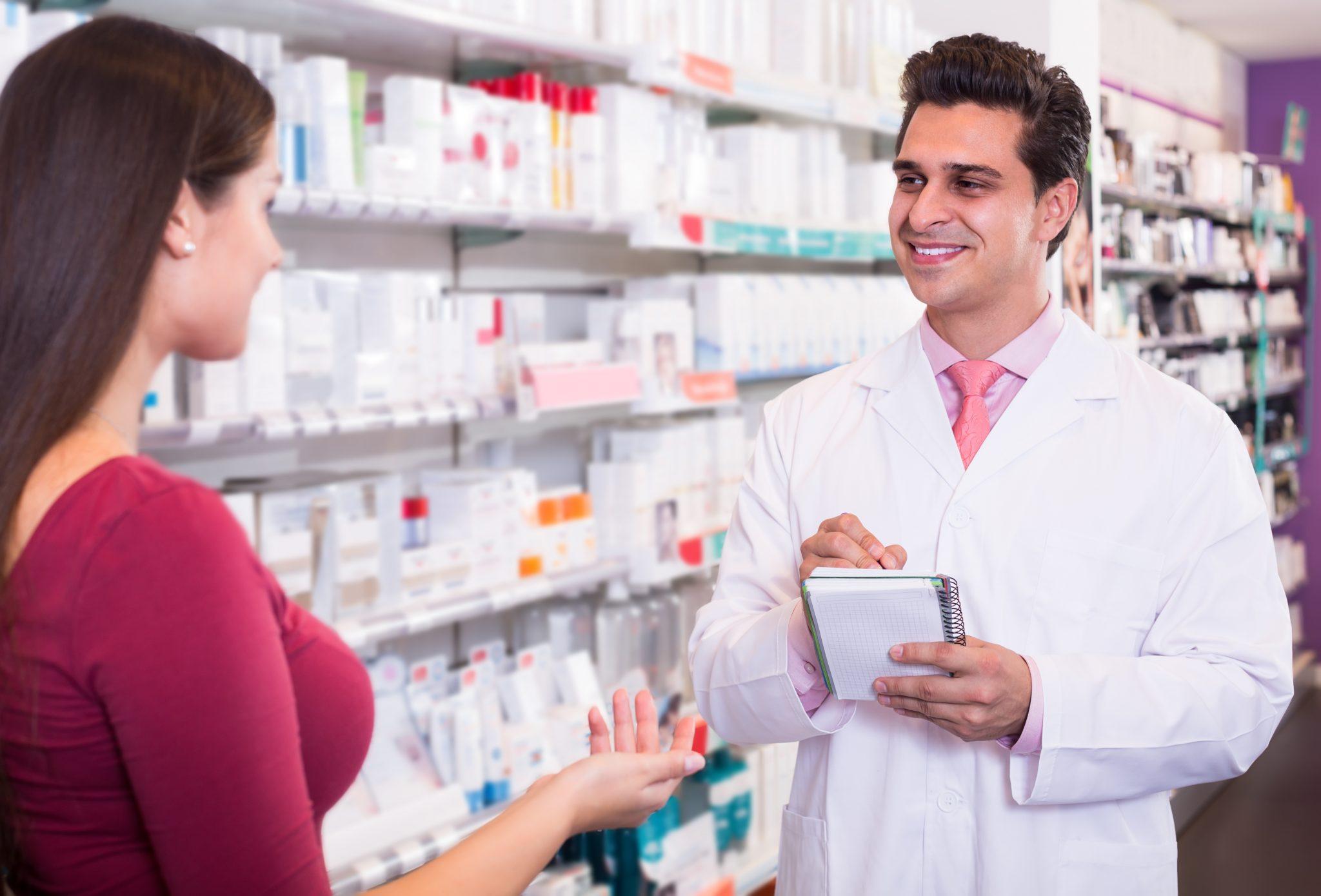 Centrum Pharmacy - Professional pharmaceutist in drugstore helping girl